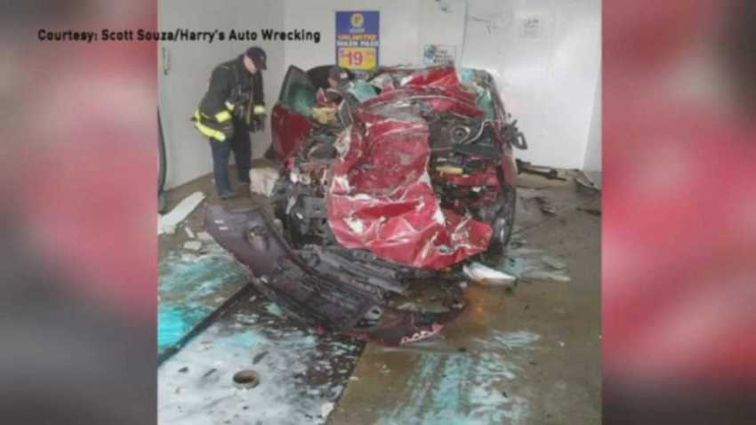 Two people were hospitalized on Sunday, Dec. 29, 2019 after a pickup truck reversed and landed atop a car at a Taunton, Massachusetts car wash.