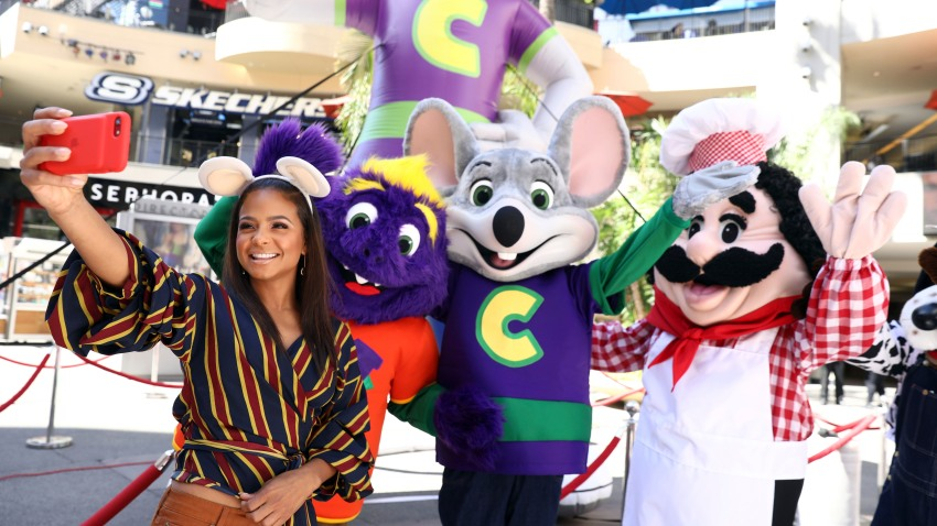 "Chuck E. Cheese mascots celebrate ""National Pizza Month"" with Christina Milian, left, on Wed., Oct. 4, 2017 in Los Angeles."
