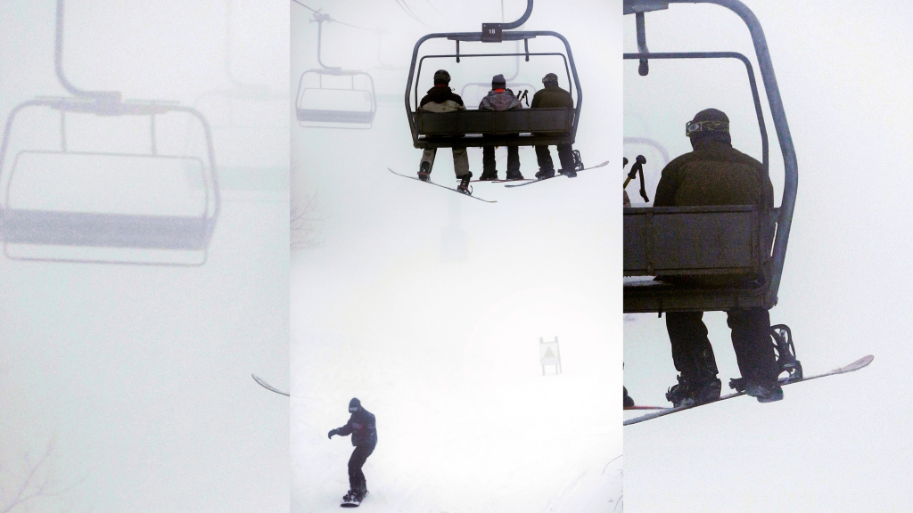 Skiers ride a chairlift, top, as a snowboarder, below, makes his way down a trail at Wachusett Mountain Ski Area, in Princeton, Mass., Thursday, Dec. 27, 2012. Areas in the north and west of the state received a blanket of heavy, wet snow on Thursday.
