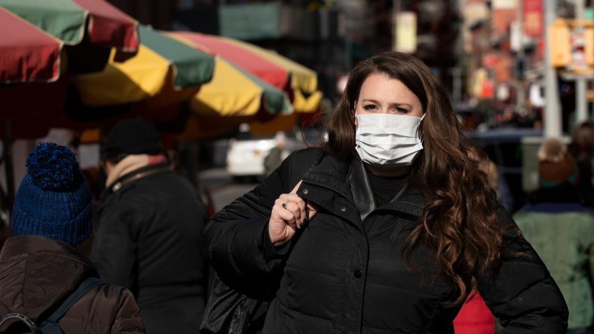 "A woman, who declined to give her name, wears a mask, Thursday, Jan. 30, 2020 in New York. She works for a pharmaceutical company and said she wears the mask out of concern for the coronavirus. ""I'd wear a mask if I were you,"" she said. For the first time in the U.S., the new virus from China has spread from one person to another, health officials said Thursday. (AP Photo/Mark Lennihan)"