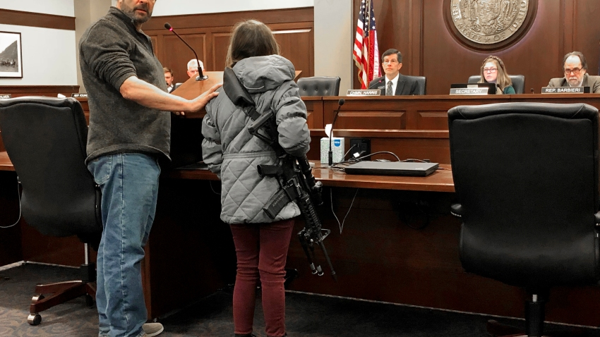 Charles Nielsen, 58, and his 11-year-old granddaughter, Bailey Nielsen, testify before a House panel at the Idaho Statehouse on Monday. Feb. 24, 2020 in Boise, Idaho. Visitors to Idaho 18 and older who can legally possess firearms would be allowed to carry a concealed handgun within city limits under legislation that headed to the House on Monday, Feb. 24. (AP Photo/Keith Ridler)