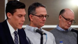 Tad Deluca, center, listens as attorney Parker Stinar addresses the media during a news conference, Thursday, Feb. 27, 2020 in Southfield, Mich. Deluca, a University of Michigan wrestler from the 1970s, says he was kicked off the team and lost his financial aid after complaining to a coach that he had been abused by a sports doctor. Deluca identified himself as the whistleblower whose 2018 complaint about the late Dr. Robert E. Anderson led to a police investigation. (AP Photo/Carlos Osorio)