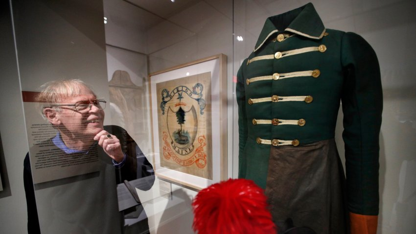 In this Friday, March 13, 2020 photo, State historian Earle Shettleworth examines a First Maine Militia uniform, probably worn by a soldier from Buckfield, on display at the Maine State Museum in Augusta, Maine.