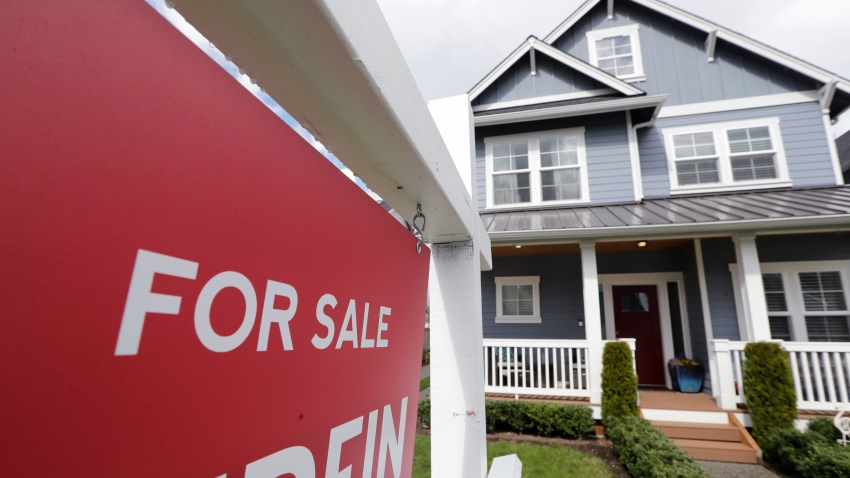 """In this Wednesday, April 1, 2020 photo, a """"For Sale"""" sign stands in front of a home that is in the process of being sold in Monroe, Wash., outside of Seattle."""