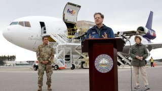 New Hampshire Gov. Chris Sununu, center, speaks to reporters as N.H. National Guard Major General David Mikolaities, left, and Sen. Jeanne Shaheen, D-N.H., right, look on, April 12, 2020, at Manchester-Boston Regional Airport, in Manchester, N.H.