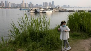 In this April 16, 2020, photo, a child wearing a mask against coronavirus rides her push bike along the banks of the Yangtze River in Wuhan in central China's Hubei province.