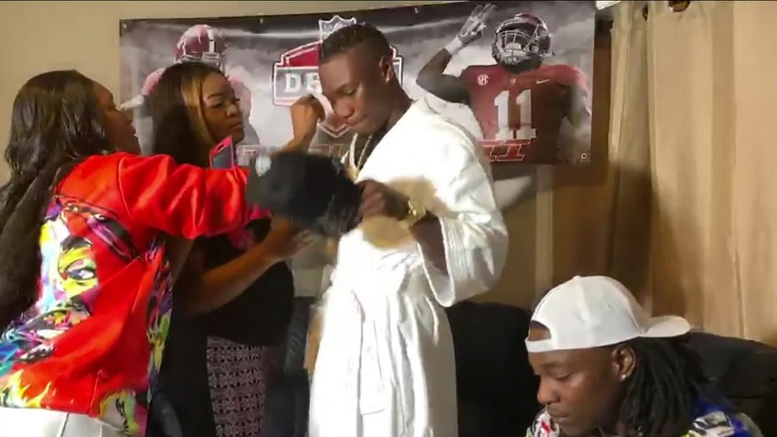 In this still image from video provided by the NFL, Henry Ruggs III, center, gets ready to put on a Las Vegas Raiders cap after being selected by the team in the first round of the NFL football draft Thursday, April 23, 2020.