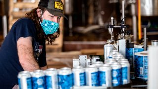 """Colin Conroy operates a labeling machine as cans of """"Fauci Spring"""" beer are labeled at Wild Heaven Beer on Thursday, April 30, 2020, in Avondale Estates, Ga."""
