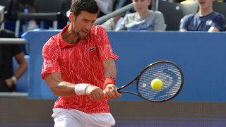 Serbia's Novak Djokovic returns the ball during an exhibition tournament in Zadar, Croatia, Sunday, June 21, 2020. Tennis player Grigor Dimitrov says he has tested positive for COVID-19 and his announcement led to the cancellation of an exhibition event in Croatia where Novak Djokovic was scheduled to play on Sunday.