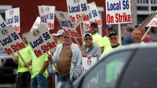 Shipbuilders picket outside an entrance to Bath Iron Works, Monday, June 22, 2020, in Bath, Maine. Thousands of workers went on strike against one of the Navy's largest shipbuilders Monday after rejecting a three-year contract.
