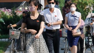 """People wearing masks walk in the Ryomyong street in Pyongyang, North Korea Friday, July 3, 2020. North Korean leader Kim Jong Un urged officials to maintain alertness against the coronavirus, warning that complacency risked """"unimaginable and irretrievable crisis,"""" state media said Friday."""