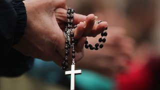 A pair of hands holds a rosary, with a cross hanging from it.
