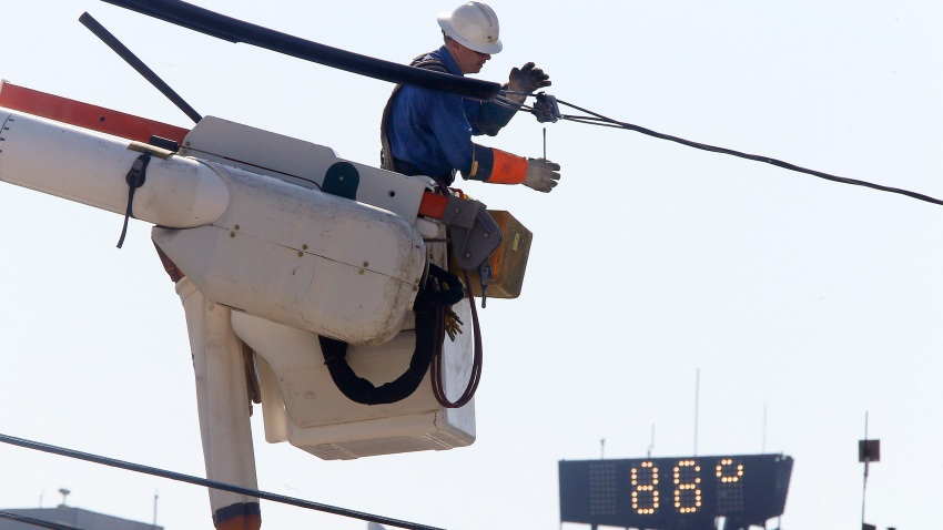 a Central Maine Power lineworker adds protective insulation to power lines
