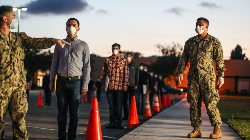 U.S. Marine recruits stand in formation as they wait in line for health screenings at the Marine Corps Recruit Depot (MCRD) on April 13, 2020