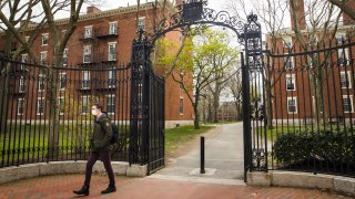 A pedestrian wearing a protective mask exits Harvard Yard on the closed Harvard University campus in Cambridge, Massachusetts, U.S., on Monday, April 20, 2020. Collegefinancial aid offices arebracingfor a spike in appeals from students finding that the aid packages they were offered for next year are no longer enough after the coronavirus pandemic cost their parents jobs or income.