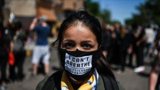 """A woman poses as she wears a mask saying """"I can't breathe"""""""