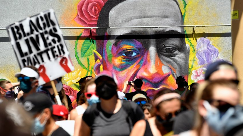 Marchers walk by a mural of George Floyd painted on a wall along Colfax Avenue on June 7, 2020, in Denver, Colorado.