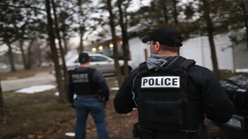 In this March 29, 2018, file photo, Customs and Border Protection officers watch a house as Homeland Security Investigations (HSI) ICE agents detain a suspected MS-13 gang member and Honduran immigrant at his home in Brentwood, New York.