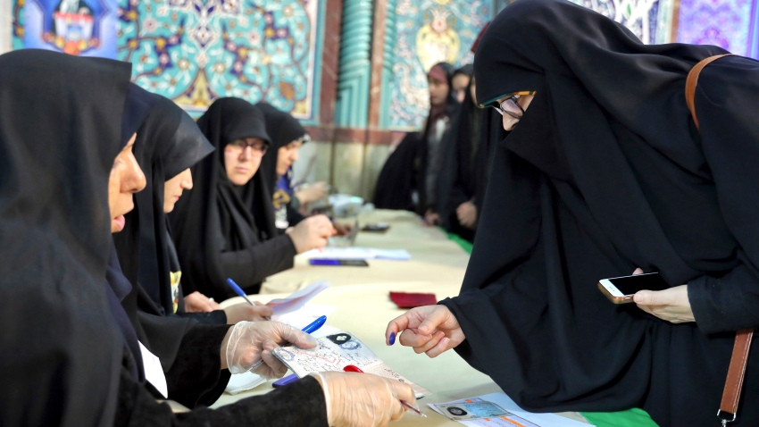 A voter registers to cast her vote during the parliament elections at a polling station in Tehran, Iran, Friday, Feb. 21, 2020. Iranians began voting for a new parliament Friday, with turnout seen as a key measure of support for Iran's leadership as sanctions weigh on the economy and isolate the country diplomatically.