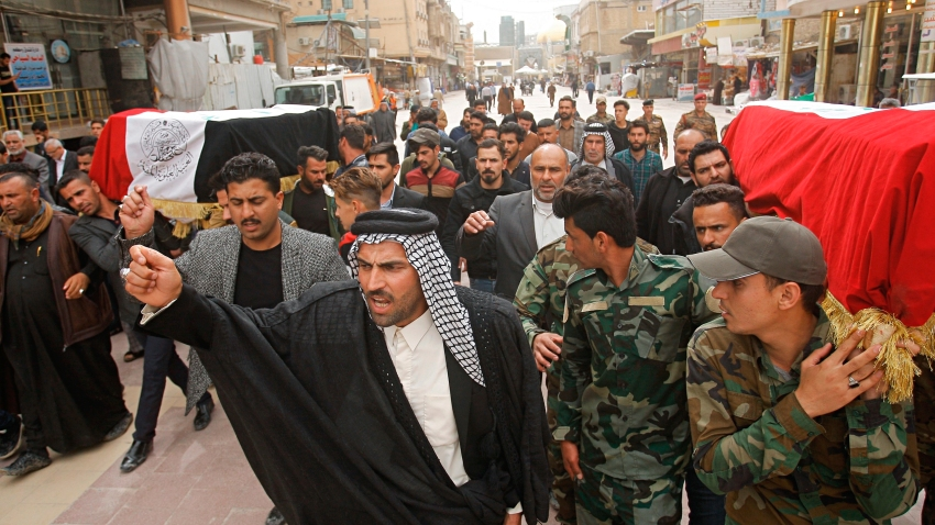 Mourners carry the flag-draped coffins of two fighters of the Popular Mobilization Forces who were killed during the US attack on against militants in Iraq, during their funeral procession at the Imam Ali shrine in Najaf, Iraq, Saturday, March 14, 2020.