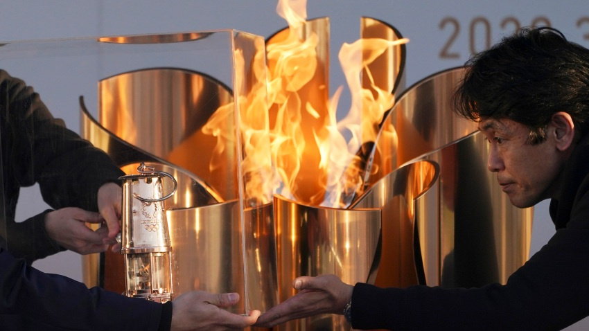 In this March 25, 2020, file, photo, officials light a lantern from the Olympic Flame at the end of a flame display ceremony in Iwaki, northern Japan.
