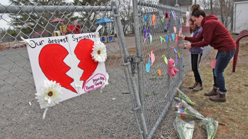 In this April 20, 2020, file photo, a woman and her daughter place a heart at a growing memorial in front of the Debert School in Debert, Nova Scotia, Canada.