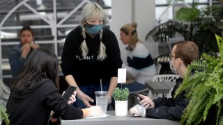 In this May 18, 2020, file photo, server Katie Maloney, of Providence, Rhode Island, center, wears a mask out of concern for the coronavirus while serving people in an outdoor seating area at Plant City restaurant in Providence, Rhode Island.