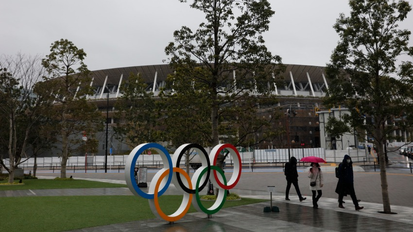 In this March 4, 2020, file photo, people walk past the Olympic rings near the New National Stadium in Tokyo.