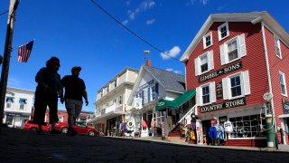 Tourists walk by newly reopened shops, Tuesday, June 9, 2020, in Boothbay Harbor, Maine.