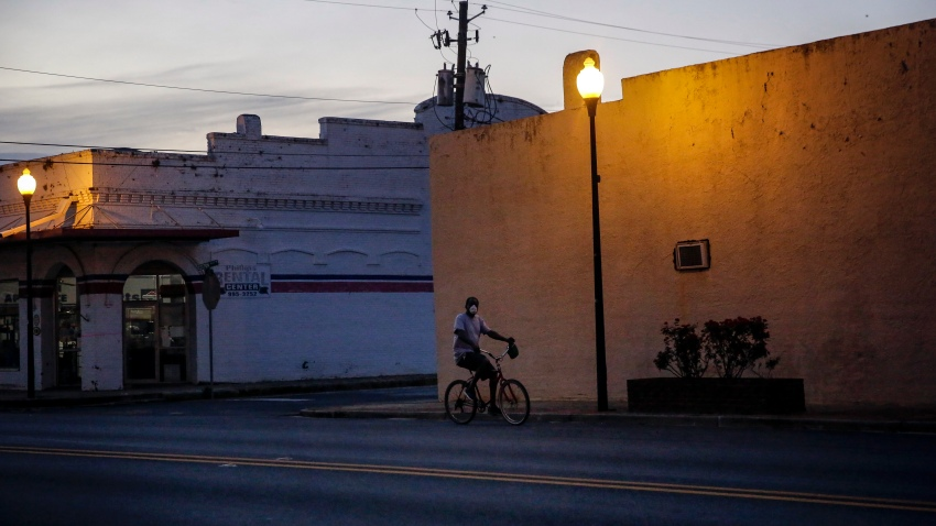 In this April 17, 2020, file photo, a man rides a bicycle down an empty street in Dawson, Georgia.