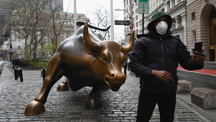 In this file photo, a man wearing a face mask takes a selfie at the Charging Bull statue on March 23, 2020, outside the New York Stock Exchange in Manhattan.