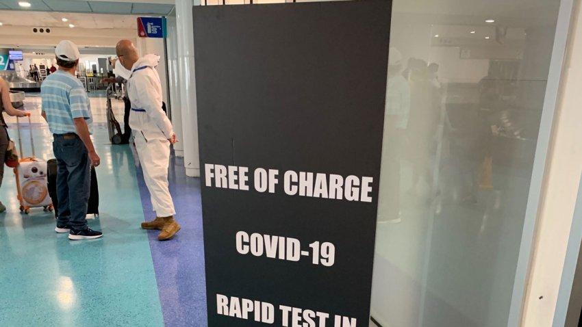 Workers steer travelers toward free testing for COVID-19 antibodies at Puerto Rico's main airport in San Juan on June 28, 2020.