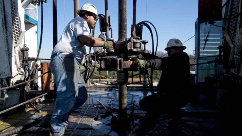 FILE: Toronto-based Trinidad Drilling Ltd. floorhands Julio Serrato, left, and Jaime Gonzalez work on the first drilling of the Reveille 1H Chesapeake Energy Corp. natural gas rig in Fort Worth, Texas, U.S., on Monday, Nov. 23, 2009. Chesapeake Energy, a shale drilling pioneer that helped to turn the United States into a global energy powerhouse, said it would file for bankruptcy protection Sunday, June 28, 2020.