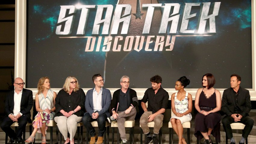 "In this Aug. 1, 2017, file photo, (L-R) executive producers Akiva Goldsman, Heather Kadin, Gretchen Berg, Aaron Harberts, and Alex Kurtzman, and actors James Frain, Sonequa Martin, Mary Chieffo, and Jason Isaacs of ""Star Trek: Discovery"" speak onstage during the CBS portion of the 2017 Summer Television Critics Association Press Tour at CBS Studio Center in Los Angeles, California."