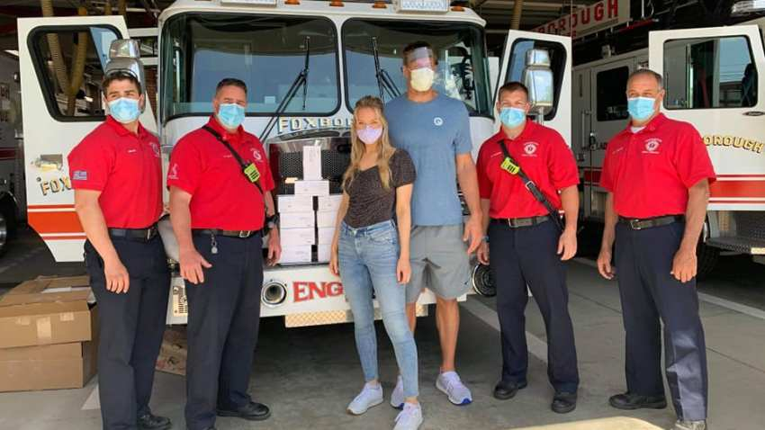 Rob Gronkowski and Camille Kostek pose with Foxboro firefighters after donating personal protective equipment