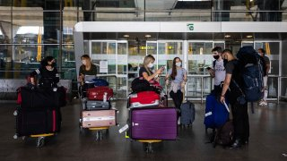 In this June 21, 2020, file photo, passengers wearing face masks arrive at Adolfo Suarez-Barajas international airport, outskirts Madrid, Spain, Sunday, June 21, 2020.
