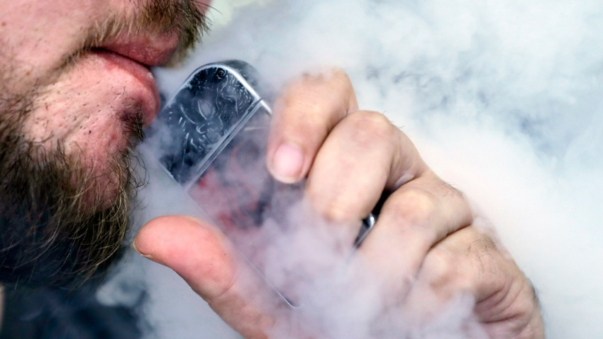 Close-up image of a man with a beard using a vaping device