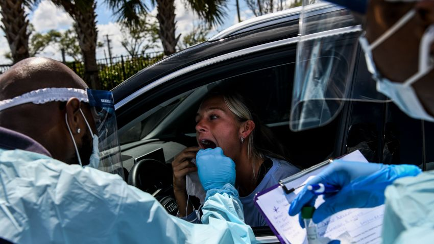 """A medical personnel member takes samples on a woman at a """"drive-thru"""" coronavirus testing lab set up by a local community center in West Palm Beach"""