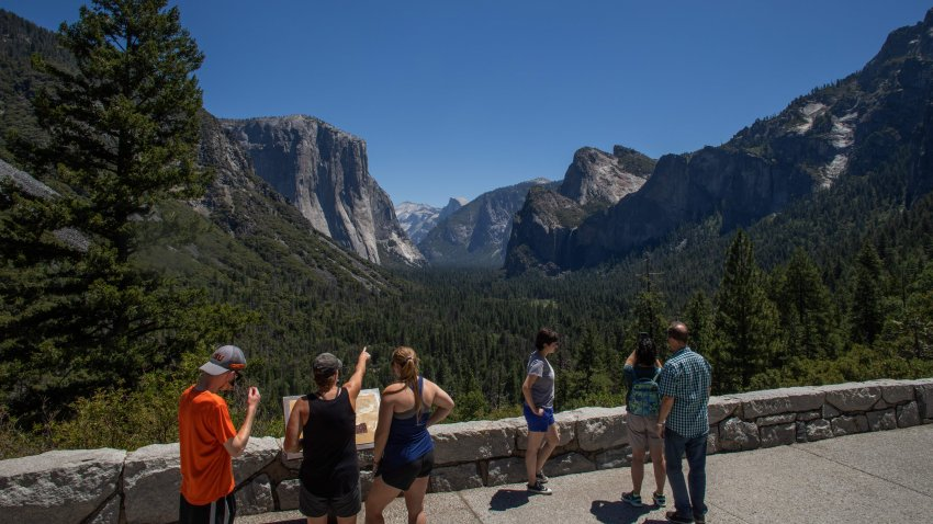 Visitors walk to the Tunnel View lookout in Yosemite Valley at Yosemite National Park, California on July 08, 2020. - After closing for 2½ months because of the coronavirus pandemic, the wildlife is taking over of areas used by the public. The park is open with limited services and facilities to those with day-use reservations, reservations for in-park lodging or camping, and wilderness or Half Dome permits.