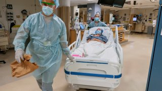 Drs. Kamen V. Vlassalov, front, and Lindsay Wahl, lead Carmen Blandin Tarleton to the operating room for her second face transplant at Brigham and Women's Hospital in Boston on July 28, 2020. Tarleton, who had her first face transplant in 2013, became the first American and only the second person globally to undergo a second face transplant procedure after her first transplant failed.