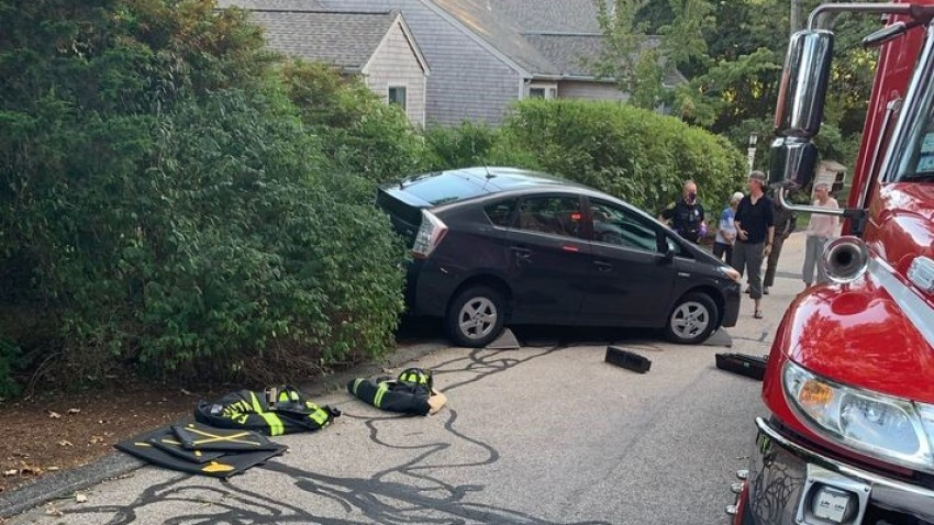 Officials say an 80-year-old woman's car backed over her, pinning her, in Falmouth, Massachusetts.