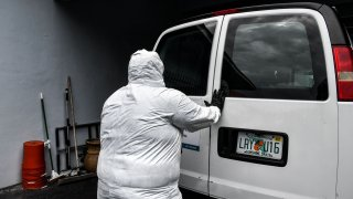 """Funeral assistant, Bradley Georges 26 pull out a stretcher from a van wearing a PPE kit prior to a funeral at one of Miami's largest funeral homes, Van Orsdel funeral homes in Miami, on July 17, 2020. - For one young funeral assistant in Florida, his social life has been dead -- his only human interactions are coronavirus victims at the funeral home where he works. But he doesn't regret his isolation. The pandemic is """"bigger than we are,"""" said Bradley Georges, 26, an assistant at the Van Orsdel funeral home in Miami."""