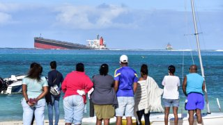 Bystanders look at MV Wakashio bulk carrier that had run aground and from which oil is leaking near Blue Bay Marine Park in south-east Mauritius on August 6, 2020.