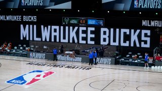 In this Aug. 26, 2020, file photo, officials stand beside an empty court after the scheduled start of game five between the Milwaukee Bucks and the Orlando Magic in the first round of the 2020 NBA Playoffs at AdventHealth Arena at ESPN Wide World Of Sports Complex in Lake Buena Vista, Florida. According to reports, the Milwaukee Bucks have boycotted their game 5 playoff game against the Orlando Magic to protest the shooting of Jacob Blake by Kenosha, Wisconsin police. NOTE TO USER: User expressly acknowledges and agrees that, by downloading and or using this photograph, User is consenting to the terms and conditions of the Getty Images License Agreement.