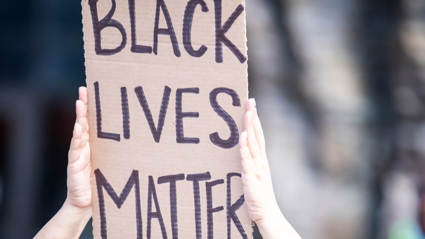 A protester holds a sign over their head that says BLACK LIVES MATTER.