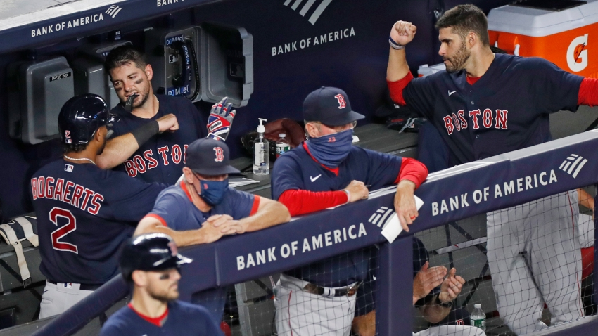 Boston Red Sox's Xander Bogaerts (2) celebrates with teammates in the dugout after hitting a fifth-inning solo home run in a baseball game against the New York Yankees, Sunday, Aug. 2, 2020, at Yankee Stadium in New York.