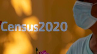 A man wearing a facemask walks past a sign encouraging people to complete the 2020 US Census, in Los Angeles, California, August 10, 2020 amid the COVID-19 pandemic.