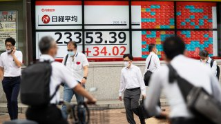 Men walk by screens showing Japan's Nikkei 225 index at a securities firm in Tokyo on Friday, Sept. 18, 2020.