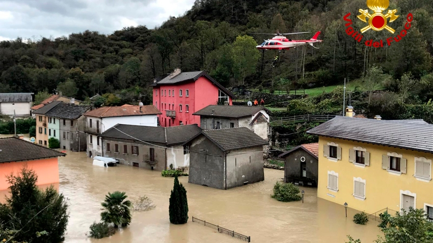 a firefighters' helicopter flies over flooding in the town of Ornavasso, in the northern Italian region of Piedmont