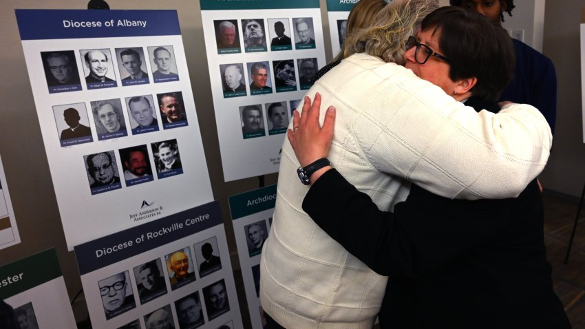 Survivor Bridget Lyons hugs a man after a press conference in New York